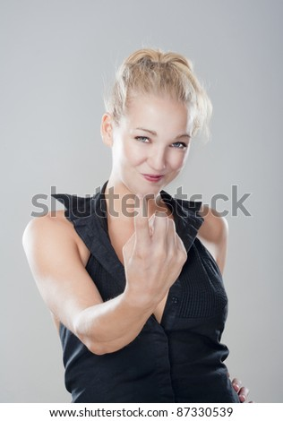 sexy blond girl showing come on gesture looking, smiling - isolated on gray - stock photo