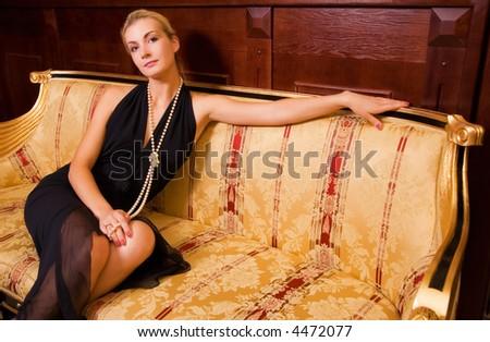 Sexy blond girl sitting on a luxury sofa - stock photo