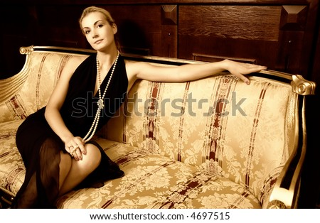 Sexy blond girl sitting on a luxury sofa (toned in sepia) - stock photo
