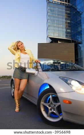 Sexy blond girl stands near modern sport car - stock photo