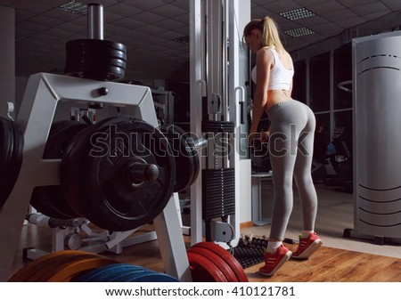 Sexy blond girl with a perfect figure and a great ass in gray leggings trains in fitness club - stock photo