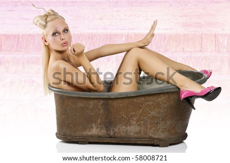 sexy blond girl with creative make up and hair style inside a bath with pink shoes - stock photo