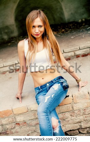sexy blond haired women sitting on obsolete ancient ruins and looking at camera - stock photo
