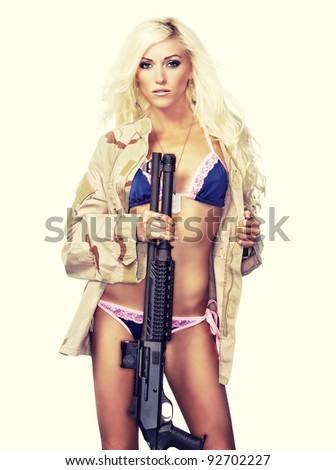 Sexy blond holding gun wearing army flak jacket - stock photo