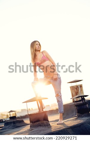 Sexy blond in in torn top with jeans open on the roof. Sunset - stock photo