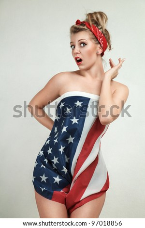 Sexy blond pin-up model wrapped in american flag - stock photo