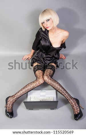Sexy blond using lap top computer - stock photo