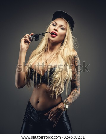 Sexy blond woman in black bra and cap holding sunglasses. Isolated on grey background.