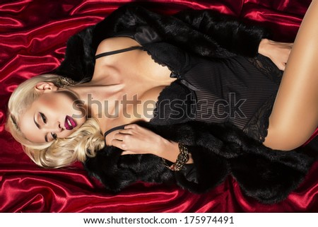 sexy blond woman in fur coat lying on the red material - stock photo