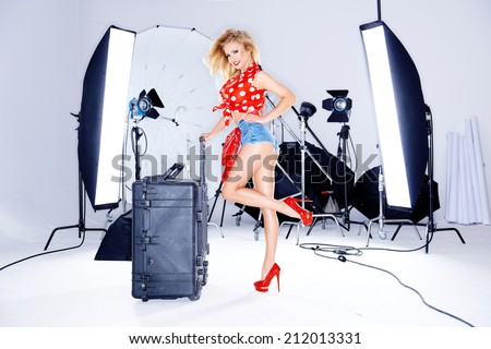 Sexy blond woman in skimpy shorts and a red polka dot top looking cheekily at the camera with a smile during a studio photo session surrounded by equipment
