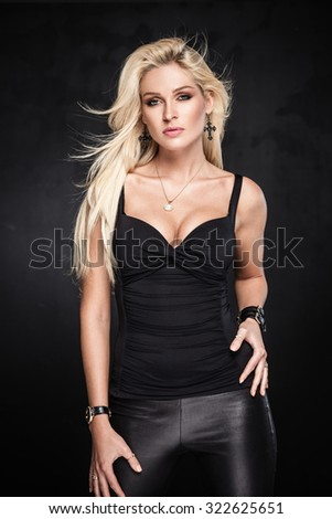 Sexy blond woman posing on dark background - stock photo