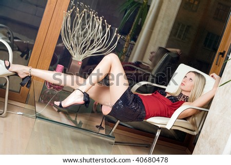 Sexy blond woman relaxing in the armchair - stock photo