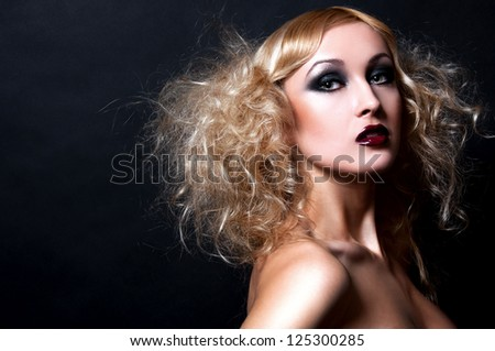 sexy blond woman with fashion make up in J G  style on black background