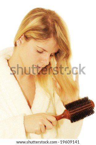 Sexy blond young woman brushing hair. - stock photo