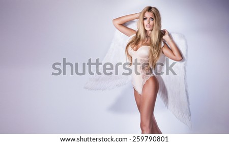 Sexy blonde beautiful woman posing with angel wings. - stock photo