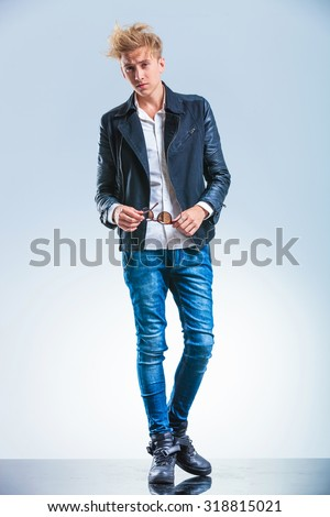 sexy blonde boy wearing jeans and leather jacket while holding sunglasses and looking forward - stock photo
