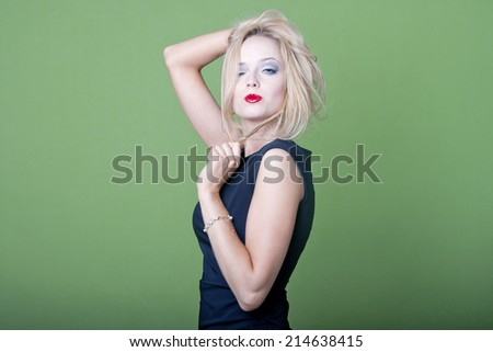 Sexy blonde businesswoman on green background - stock photo