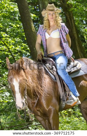 Sexy blonde cowgirl riding on her horse in the woods. - stock photo