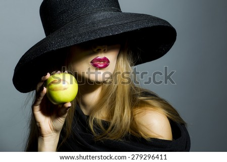 Sexy blonde girl in retro black hat with bright make up holding fresh green apple standing on gray background copyspace, horizontal picture - stock photo