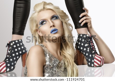 sexy blonde girl with euro flag make-up and glitter dress with two shoes with american flag design, she looks up at right and takes the ankle of the model behind her - stock photo