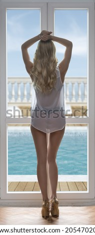 sexy blonde girl with long wavy hair turned on her back near window with heels, sexy transparent shirt and sexy panties, sensual body  - stock photo