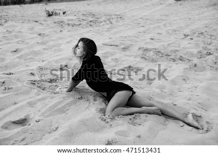 sexy blonde haired young woman posing in sands of desert lit by setting sun light
