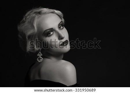 Sexy blonde in black dress on a dark background. Vintage dress and beautiful jewelry. Professional makeup. Photo for fashion magazines, posters and websites.