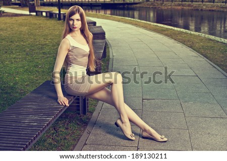 sexy blonde lady sitting on a bench in the park  - stock photo