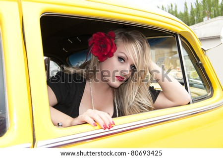Sexy blonde pin up girl sitting inside classic car - stock photo