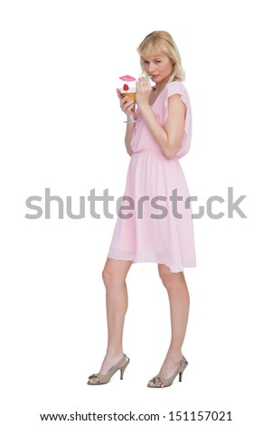 Sexy blonde posing while drinking cocktail against white background - stock photo