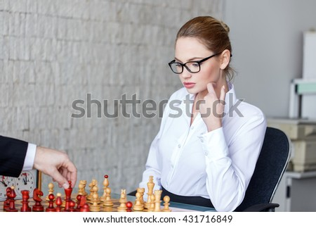 Sexy blonde secretary playing chess with boss in office