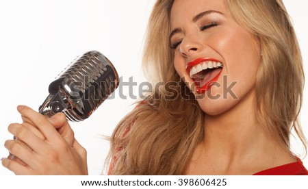 sexy blonde singer singing to retro microphone on white