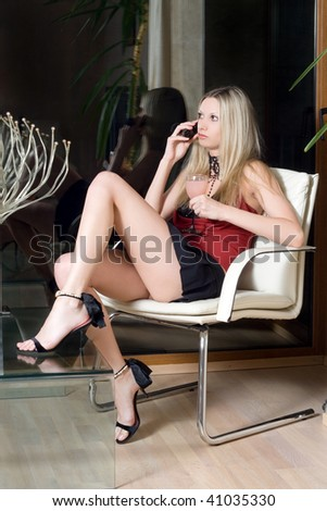Sexy blonde with a glass of cocktail speaking on the phone - stock photo