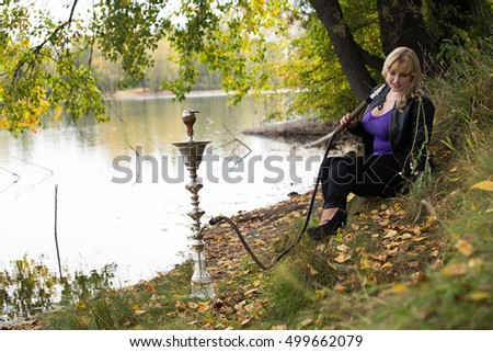 sexy blonde with big breasts smokes a hookah on the nature of the lake