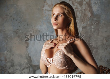 Sexy blonde with big tits in a gentle lingerie stands near the sofa. Lingerie provakator agent. Sexy girl. A slim body. The girl holds hands behind boobs. Perfect body in an elegant interior. Portrait