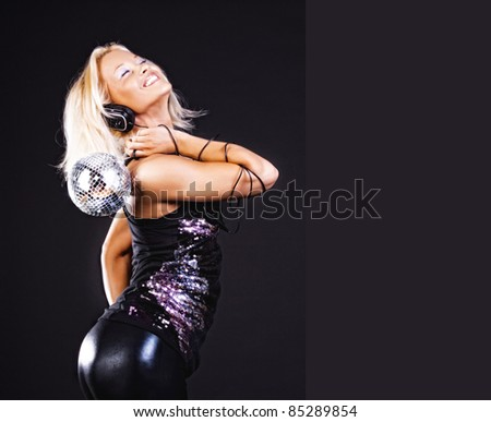 Sexy blonde with disco ball enjoys music at party - stock photo