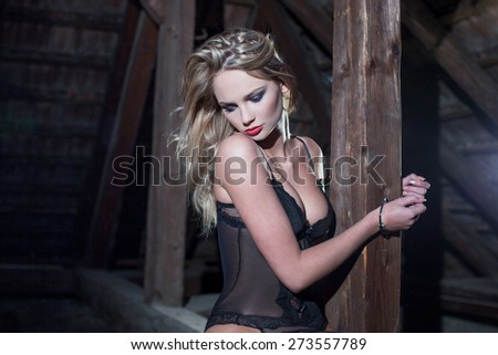 Sexy blonde woman cuffed to timber, bdsm - stock photo