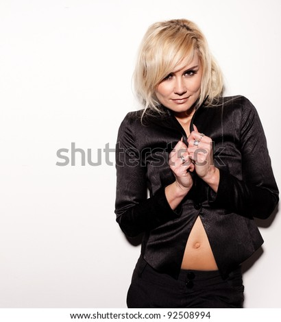 Sexy blonde woman dressed in slacksuit pulling the lapels over her breasts while showing her belly button. - stock photo