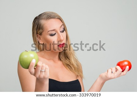 Sexy blonde woman holding apple and tomato