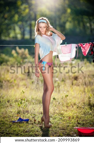Sexy blonde woman in bikini putting clothes to dry in sun. Sensual fair hair young female on high heels putting out the washing to dry in sunny day. Perfect body housewife, outdoor shot