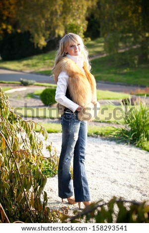 Sexy blonde woman in jeans standing on walkway in park
