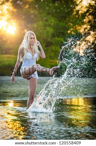 Sexy blonde woman in lingerie in a river water.Sexy young woman relaxing on the beach.Young, beautiful woman in the evening swim in the river.Beautiful young woman in a white bathing in the river.
