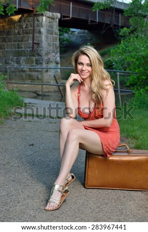 Sexy blonde woman in red dress sitting next to road or path on vintage suitcase - stock photo