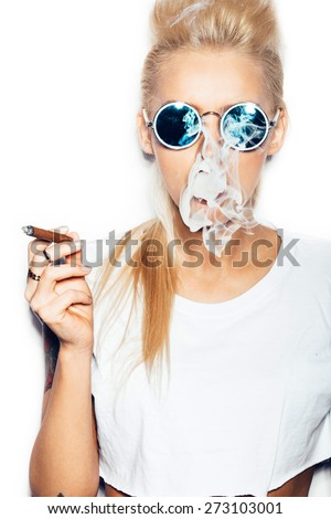Sexy blonde woman in sunglasses and white t-shirt blowing smoke from a cigar. Swag style girl with bright make-up and hairstyle. White background, not isolated - stock photo