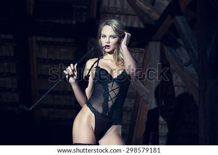 Sexy blonde woman in underwear bite whip at barn, bdsm - stock photo