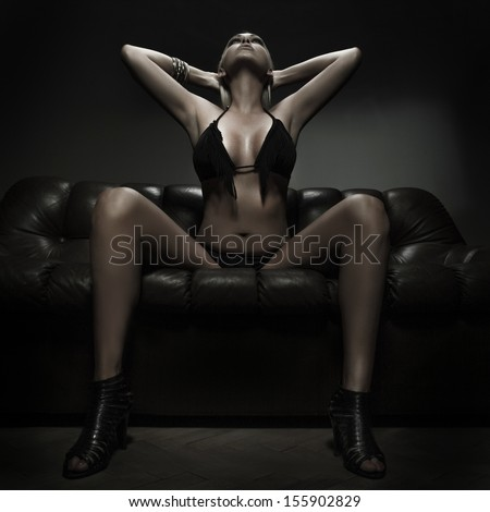 Sexy blonde woman looking up on sofa - stock photo
