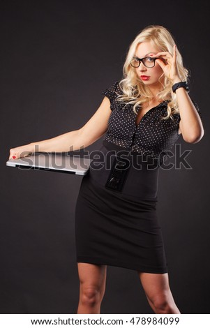 Sexy blonde woman posing with laptop in studio