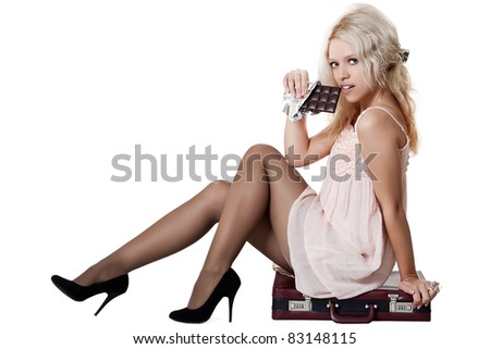Sexy blonde woman seating on case and eating chocolate - stock photo