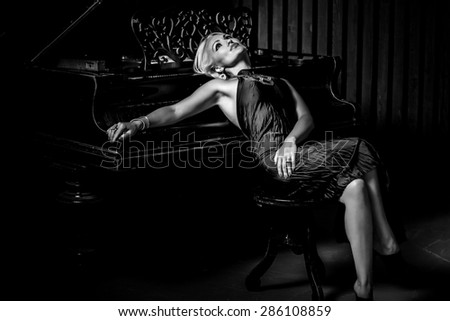 sexy blonde woman sitting near piano. Black and White Fashion studio portrait - stock photo