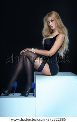 Sexy blonde woman sitting, wearing elegant lingerie and stockings. Studio shot. - stock photo